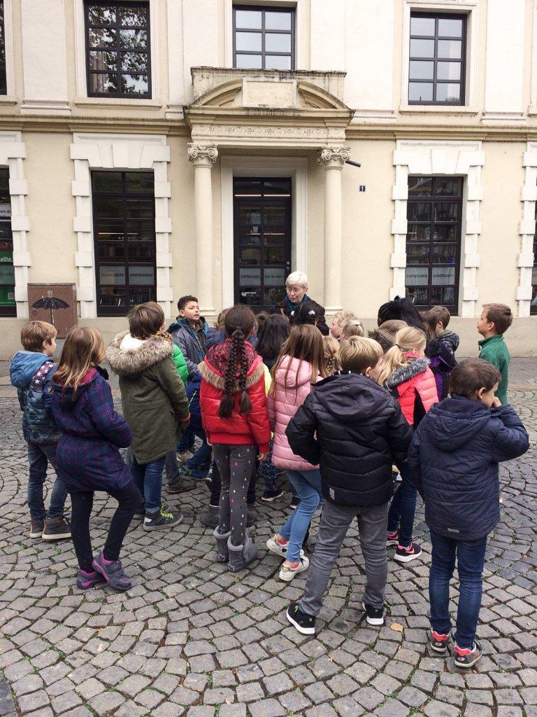 Die Kinder lauschen den Erzählungen vor dem Rathaus.