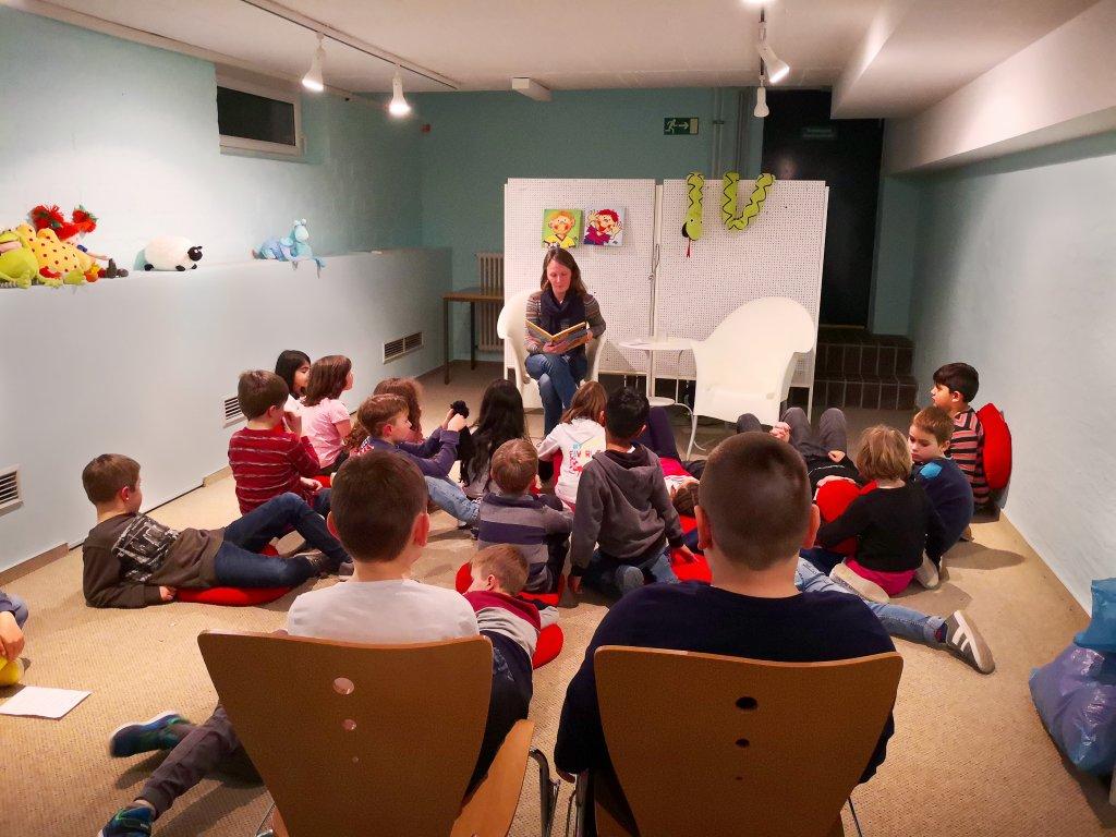 Die Kinder bekommen eine Geschichte vorgelesen.
